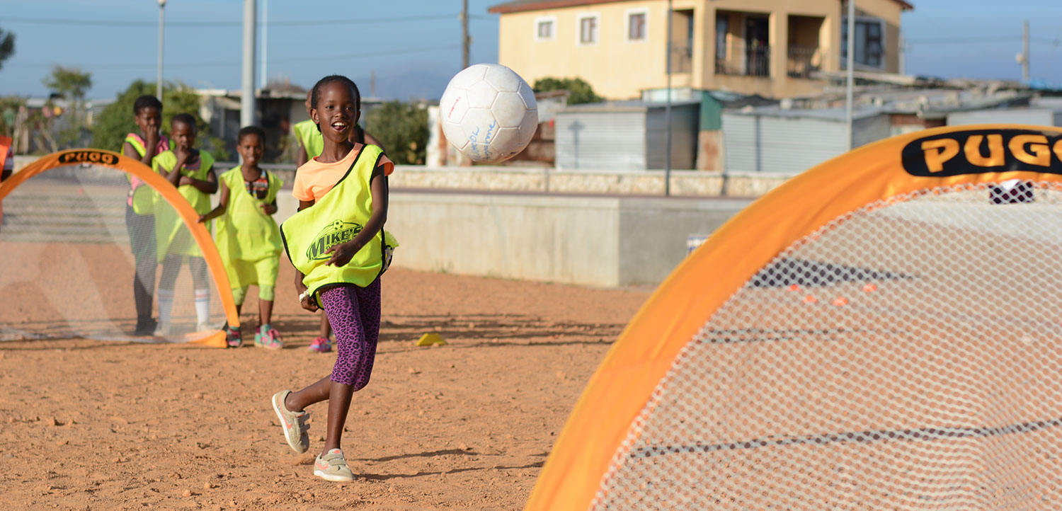 Girl in Africa shooting on a Pugg soccer gaol - Grassroots Soccer and Pugg partnership image
